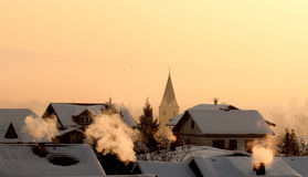 Cold morning. Very cold morning over houses and church roofs, smoke rises from chimney Stock Photography