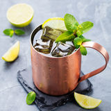Cold Moscow Mules cocktail with ginger beer, vodka, lime. Grey stone background Royalty Free Stock Photo