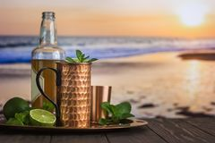 Cold Moscow Mules cocktail. With ginger beer, vodka and lime over beach and seaside background royalty free stock images