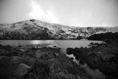 Cold mountain lake. A cold and bleak view of a lake in winter.Shown in black and white,surrounding mountains are covered in snow and ice Royalty Free Stock Photos