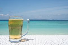 Cold mug of beer on the table at the beach restaurant. Cold mug of beer on the white rattan table at the beach restaurant with beautiful blue sea and sky stock photo