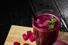 Cold, natural and organic red beet juice. A glass of beetroot drink on a wooden background. Beet cut in cubes on a desk. Royalty Free Stock Images
