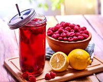 Cold non alcoholic cocktail with lemon half and raspberries bowl. Nonalcoholic beverage in cocktail glass with cocktail straw on wooden board. Table setting Stock Photos
