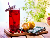 Cold non alcoholic cocktail with lemon half and raspberries. Nonalcoholic beverage in cocktail glass with cocktail straw on wooden board. Table setting rural Royalty Free Stock Photography