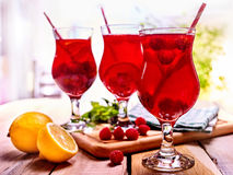 Cold non alcoholic cocktail with lemon slice and raspberries. Lemonade in glass with straw on wooden board. Table setting rural style for meeting friends in Royalty Free Stock Photography