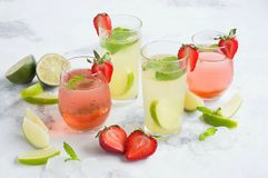 Cold, non alcoholic cocktails. Iced tea with strawberries and mint and lemonade with lime and mint. On a white background stock photos
