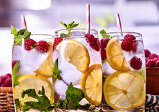 Cold non alcoholic cocktails with lemon slice and raspberries. Cold water with lemon and mint leaf. Fresh raspberries lemonade and ice cubes. Table setting Stock Photography