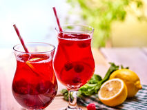 Cold nonalcoholic cocktail with lemon slice and raspberries. Cold non alcoholic cocktail with lemon slice and raspberries. Lemonade in glass with straw on Royalty Free Stock Photography