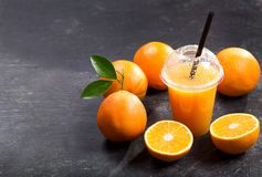 Cold orange juice in takeaway plastic cup with fresh fruits. On dark table royalty free stock images
