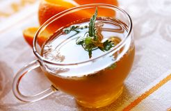 Cold orange-mint tea. A glass cap of cold orange-mint tea with ice, closeup Stock Photography