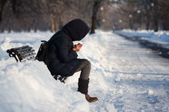 Cold outside. Lonely person with hoodie and backpack staying on a bench in city park alley with snow in winter time and being cold royalty free stock photos