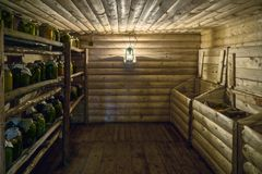 Cold pantry. Cold rural wooden pantry with jars on shelves and cereals in chests. Lantern lights on the wall. Horizontal shot stock image