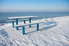 Cold picnic table in wintertime. Snowy picnic table and bench along the dutch coast royalty free stock image