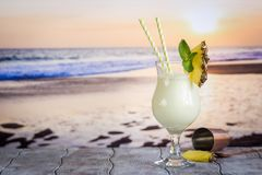 Cold pina colada cocktail. In a glass on the beach with seascape background royalty free stock photo