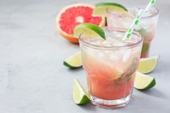 Cold pink cocktail with fresh grapefruit, lime and ice cubes, paloma, copy space. Cold pink cocktail with fresh grapefruit, lime and ice cubes on concrete royalty free stock image