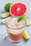 Cold pink cocktail with fresh grapefruit, lime and ice, vertical Royalty Free Stock Photo