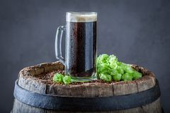 Cold pint of dark beer on old barrel. Cold pint of dark beer on old wooden barrel royalty free stock images