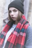 Cold portrait of a young attractive girl in a cap coat and red scarf in the cold season stock photo