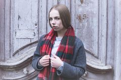 Cold portrait of a young offended attractive girl in a coat and red scarf in the cold season on the background of an old stock images