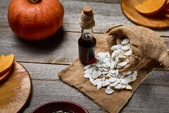 Free Cold Pressed Pumpkin Seed Oil In A Glass Bottle, Raw Pampkin Decorated With Seeds In Sackcloth Bag And Wooden Table Royalty Free Stock Photo - 172940475