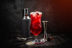 Cold red cocktail. And shaker on dark background royalty free stock photography