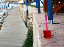 Cold red drink with straw at the beach. Photo of cold red drink with straw at the beach royalty free stock images