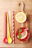 Cold red soft drink from raspberry syrup and mint. With red straw on wooden board Stock Images