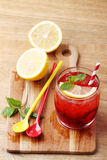 Cold red soft drink from raspberry syrup and mint. With red straw on wooden board Stock Photography