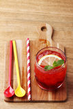 Cold red soft drink from raspberry syrup and mint. With red straw on wooden board Stock Photo