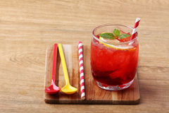 Cold red soft drink from raspberry syrup and mint. With red straw on wooden board Royalty Free Stock Image
