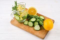 Cold and refreshing detox water with lemon, cucumber, rosemary and ice in glass jar. stock photo