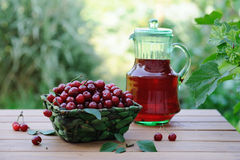 Cold refreshing drink from cherries in a pitcher and ripe berries in basket on wooden table Royalty Free Stock Photography