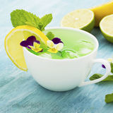 Cold refreshing drink with mint syrup, ice cubes, mint, lemon, edible flowers of a garden viola on a light turquoise Royalty Free Stock Photo
