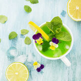 Cold refreshing drink with mint syrup, ice cubes, mint, lemon, edible flowers of a garden viola on a light turquoise Royalty Free Stock Image