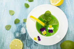 Cold refreshing drink with mint syrup, ice cubes, mint, lemon, edible flowers of a garden viola on a light turquoise Stock Image