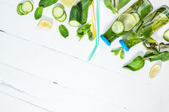 Cold and refreshing infused detox water with lime, mint and cucumber in a bottle on white wood background Royalty Free Stock Photos