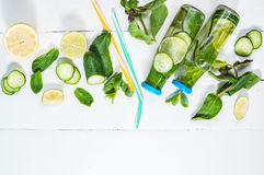 Cold and refreshing infused detox water with lime, mint and cucumber in a bottle on white wood background. Copyspace and. Top view Royalty Free Stock Photography