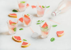 Cold refreshing summer alcohol cocktail with fresh grapefruit pieces. Flat-lay of cold refreshing summer alcohol cocktail with fresh grapefruit, mint and ice in Royalty Free Stock Images
