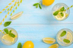 Cold refreshing summer drink with lemon and mint on light blue wooden background. Cold refreshing summer drink with lemon and mint on light blue wooden Stock Image