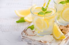 Cold refreshing summer drink with lemon and mint on wooden background. Cold refreshing summer drink with lemon and mint on wooden background, selective focus Stock Photo