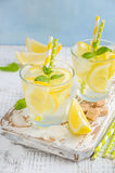 Cold refreshing summer drink with lemon and mint on wooden background. Royalty Free Stock Photos