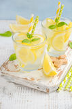 Cold refreshing summer drink with lemon and mint on wooden background. Stock Photos
