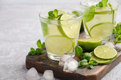 Cold refreshing summer drink with lime and mint in a glass on a grey concrete or stone background. Stock Photography