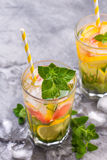 Cold refreshing summer lemonade in a glass on a grey concrete or stone background. stock photography
