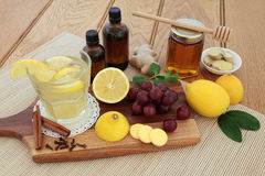 Cold Remedy Food and Drink. Cold remedies with cough medicine, vitamin c tablets, honey, grapes, spices and hot lemon drink on maple board over bamboo and oak Royalty Free Stock Photos
