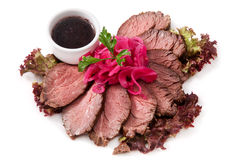 Cold roast beef with sauce and onions. Cold Roast beef sliced with sauce, onions and herbs Stock Images
