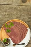 Cold roast beef on a wooden table. Delicacy of beef. Preparing cold refreshments. Traditional meal. Royalty Free Stock Photography