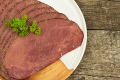 Cold roast beef on a wooden table. Delicacy of beef. Preparing cold refreshments. Traditional meal. Stock Image
