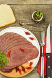 Cold roast beef on a wooden table. Delicacy of beef. Preparing cold refreshments. Traditional meal. Royalty Free Stock Image