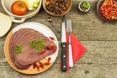 Cold roast beef on a wooden table. Delicacy of beef. Preparing cold refreshments. Traditional meal. Stock Photos